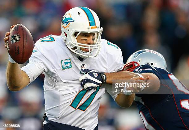 Ryan Tannehill of the Miami Dolphins is sacked during the fourth quarter against the New England Patriots at Gillette Stadium on December 14 2014 in...