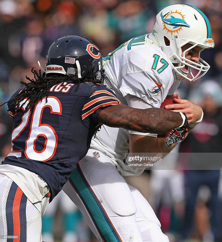 Ryan Tannehill #17 of the Miami Dolphins is tackled by Tim Jennings #26 of the Chicago Bears after a 30-yard first down run during the third quarter at Soldier Field on October 19, 2014 in Chicago, Illinois.