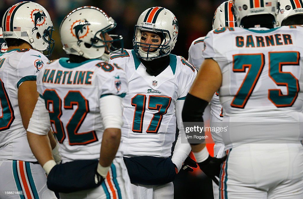 <a gi-track='captionPersonalityLinkClicked' href=/galleries/search?phrase=Ryan+Tannehill&family=editorial&specificpeople=5573174 ng-click='$event.stopPropagation()'>Ryan Tannehill</a> #17 of the Miami Dolphins stands in a huddle with his teammates against the New England Patriots in the second half at Gillette Stadium on December 30, 2012 in Foxboro, Massachusetts.