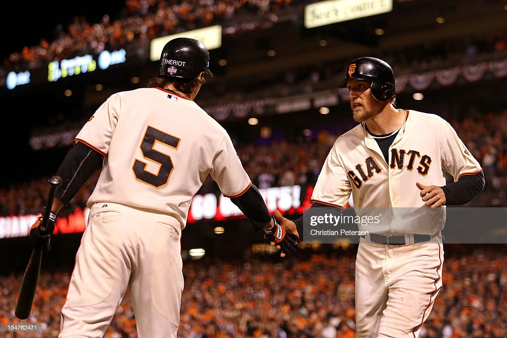 Ryan Theriot #5 and Hunter Pence #8 of the San Francisco Giants celebrate after Pence scored on a double play ball hit by Brandon Crawford #35 oin the seventh inning against the Detroit Tigers during Game Two of the Major League Baseball World Series at AT&T Park on October 25, 2012 in San Francisco, California.