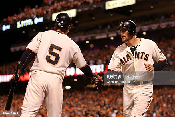 Ryan Theriot and Hunter Pence of the San Francisco Giants celebrate after Pence scored on a double play ball hit by Brandon Crawford oin the seventh...