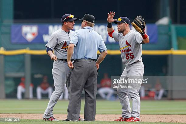 Ryan Theriot and Skip Schumaker of the St Louis Cardinals argue a call with second base umpire Mike Muchlinski during the game against the Cincinnati...