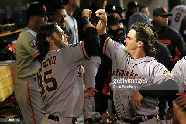 Ryan Theriot of the San Francisco Giants celebrates with teammate Brandon Crawford in the dugout after scoring a run off of Marco Scutaro of the San...
