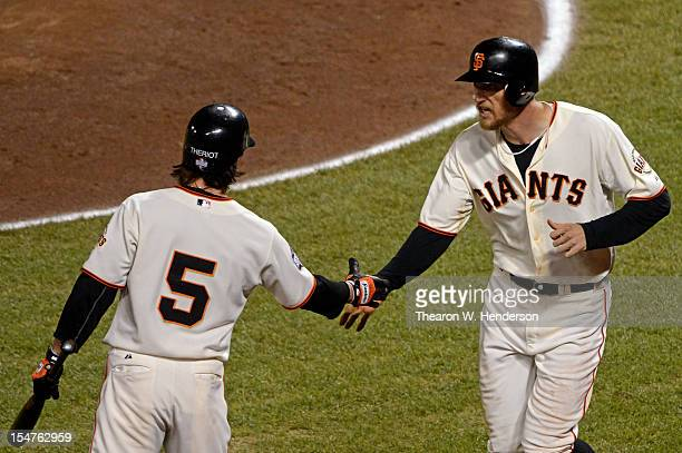 Ryan Theriot of the San Francisco Giants greets Hunter Pence after Pence drove in Angel Pagan on a sacrifice fly in the eighth inning against the...