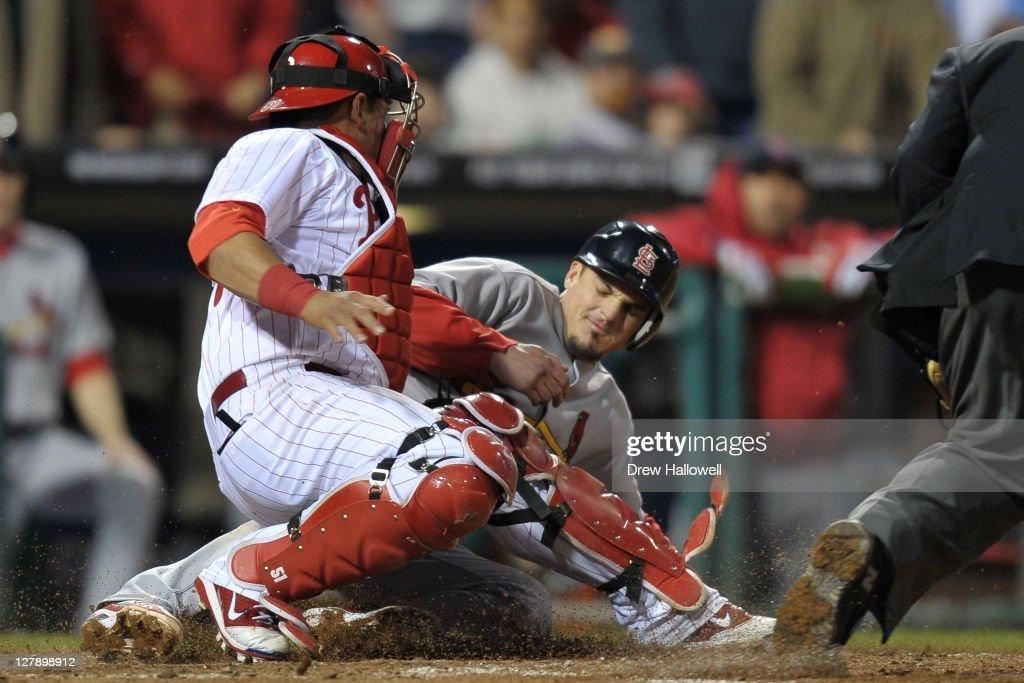 Ryan Theriot #3 of the St. Louis Cardinals slides in to home plate safe to scoring the game tying run in the sixth inning of Game Two of the National League Division Series against the Philadelphia Phillies at Citizens Bank Park on October 2, 2011 in Philadelphia, Pennsylvania.