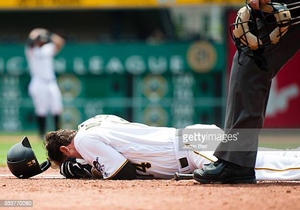 Ryan Vogelsong of the Pittsburgh Pirates lays on the ground after being hit in the head by a pitch thrown by Jordan Lyles of the Colorado Rockies in...