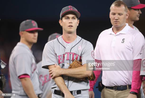 Ryan Weber of the Seattle Mariners exits the game with arm pain with the trainer beside him in the fourth inning during MLB game action against the...