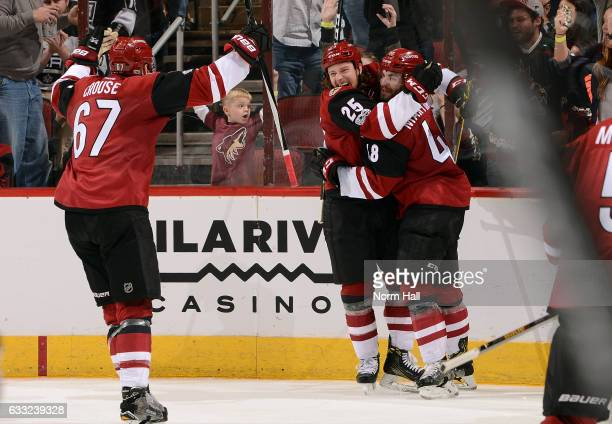 Ryan White of the Arizona Coyotes celebrates with teammate Jordan Martinook and Lawson Crouse after scoring a second period goal against the Los...