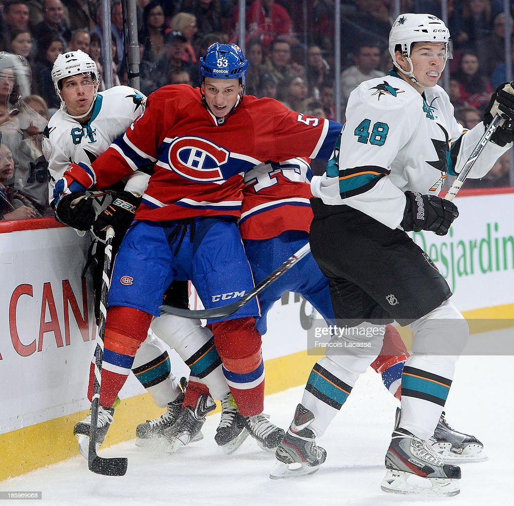 Ryan White #53 of the Montreal Canadiens checks into the boards Justin Braun #61 of the San Jose Sharks while Tomas Hertl #48 watches the action during the NHL game on October 26, 2013 at the Bell Centre in Montreal, Quebec, Canada.