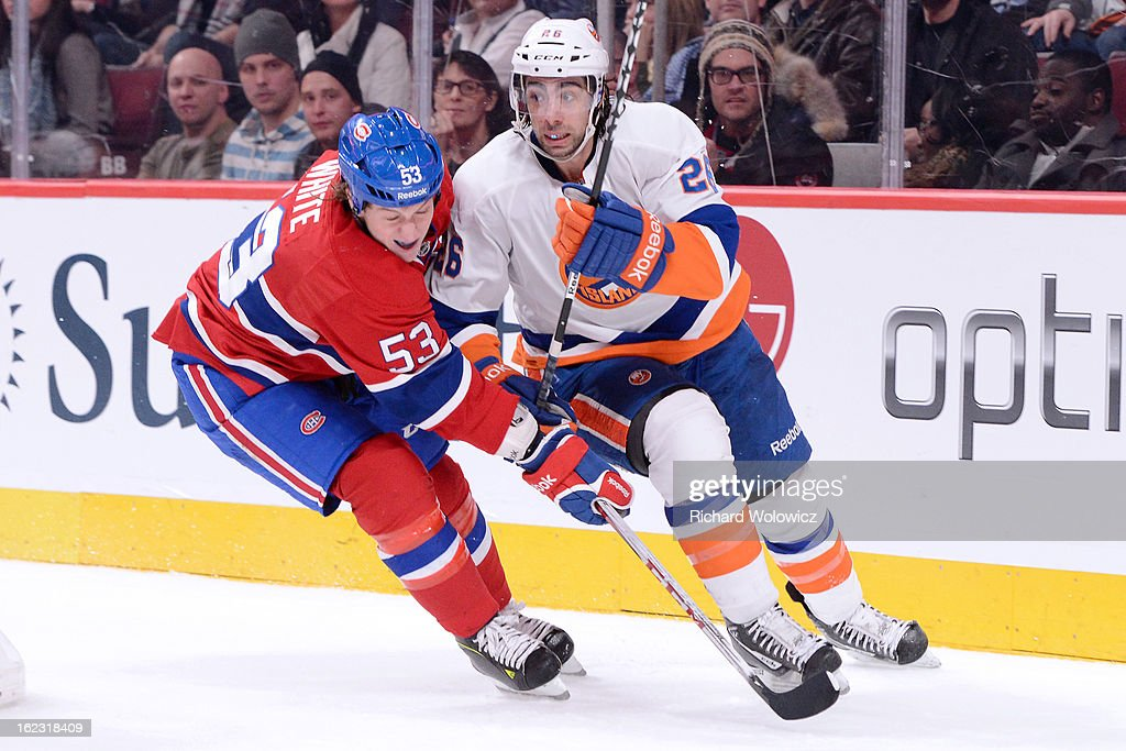 <a gi-track='captionPersonalityLinkClicked' href=/galleries/search?phrase=Ryan+White&family=editorial&specificpeople=225044 ng-click='$event.stopPropagation()'>Ryan White</a> #53 of the Montreal Canadiens defends against <a gi-track='captionPersonalityLinkClicked' href=/galleries/search?phrase=Matt+Moulson&family=editorial&specificpeople=3365493 ng-click='$event.stopPropagation()'>Matt Moulson</a> #26 of the New York Islanders during the NHL game at the Bell Centre on February 21, 2013 in Montreal, Quebec, Canada. The Islanders defeated the Canadiens 4-3 in overtime.