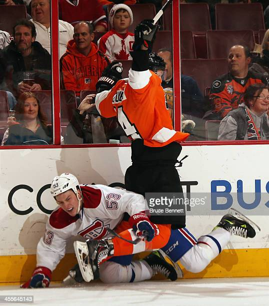 Ryan White of the Montreal Canadiens is hit into the boards by Sean Couturier of the Philadelphia Flyers during the first period at the Wells Fargo...