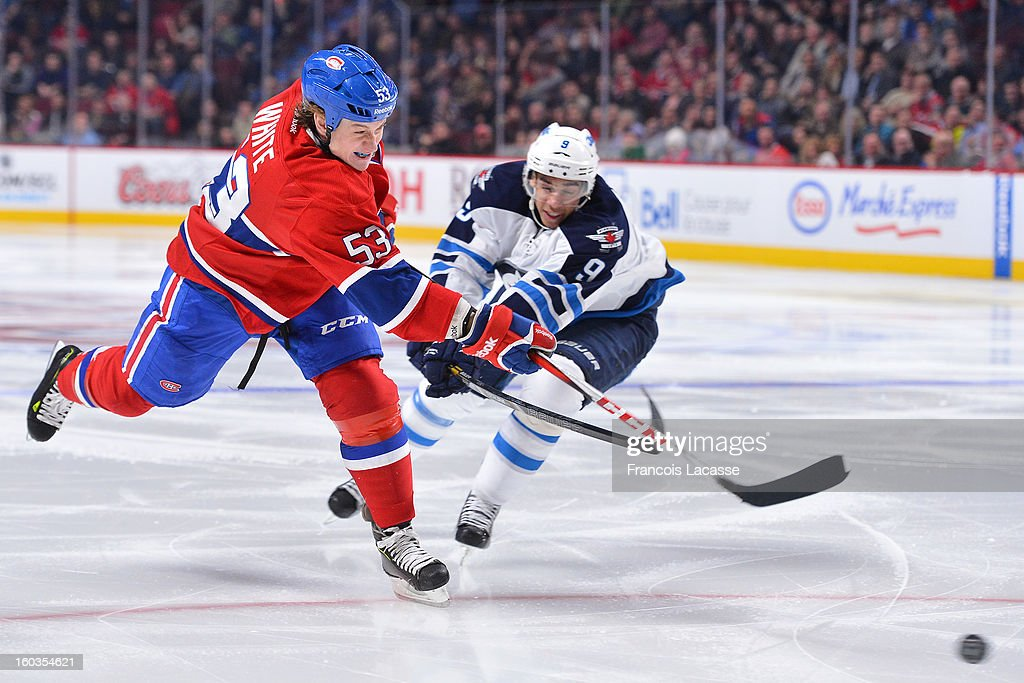 <a gi-track='captionPersonalityLinkClicked' href=/galleries/search?phrase=Ryan+White&family=editorial&specificpeople=225044 ng-click='$event.stopPropagation()'>Ryan White</a> #53 of the Montreal Canadiens takes a shot past <a gi-track='captionPersonalityLinkClicked' href=/galleries/search?phrase=Evander+Kane&family=editorial&specificpeople=4303789 ng-click='$event.stopPropagation()'>Evander Kane</a> #9 of the Winnipeg Jets in NHL action on January 29, 2013 at the Bell Centre in Montreal, Quebec, Canada.