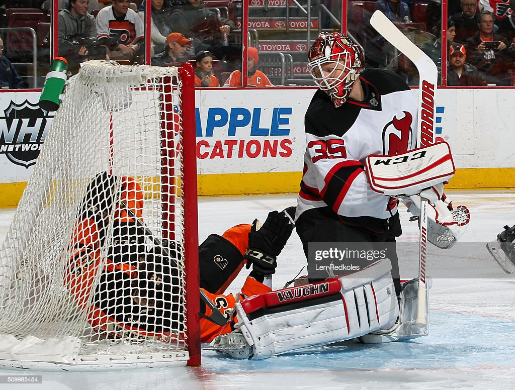 <a gi-track='captionPersonalityLinkClicked' href=/galleries/search?phrase=Ryan+White&family=editorial&specificpeople=225044 ng-click='$event.stopPropagation()'>Ryan White</a> #25 of the Philadelphia Flyers ends up in the net of <a gi-track='captionPersonalityLinkClicked' href=/galleries/search?phrase=Cory+Schneider&family=editorial&specificpeople=696908 ng-click='$event.stopPropagation()'>Cory Schneider</a> #35 of the New Jersey Devils after tripping in the offensive zone on February 13, 2016 at the Wells Fargo Center in Philadelphia, Pennsylvania.