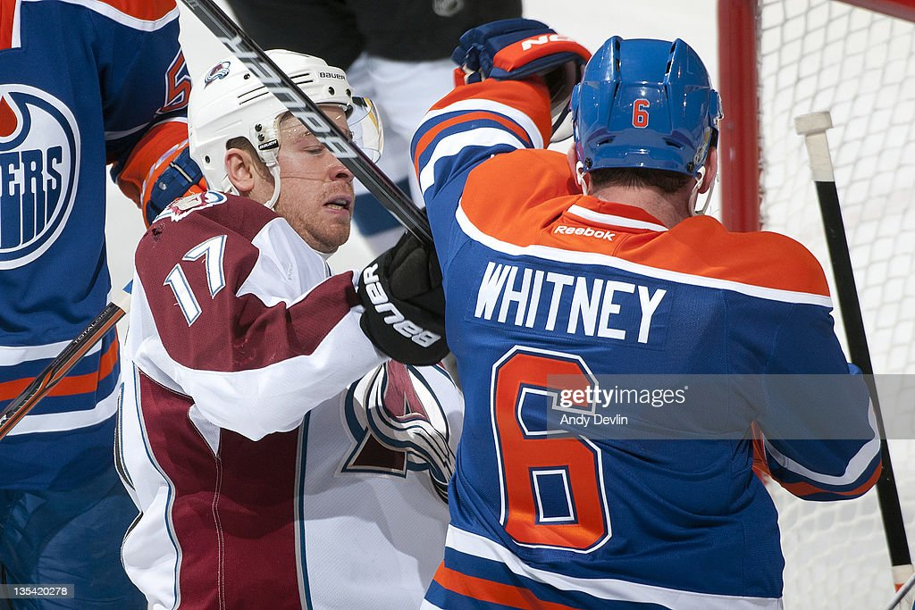 Ryan Whitney of the Edmonton Oilers shoves Chuck Kobasew of the Colorado Avalanche in front of the net at Rexall Place on December 9 2011 in Edmonton...