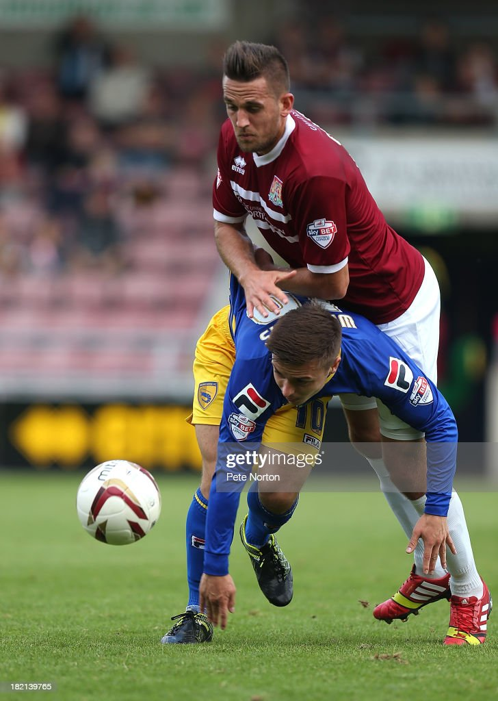 Ryan Williams of Morecambe attempts to move away with the ball under pressure from Darren Carter of Northampton Town during the Sky Bet League Two match between Northampton Town and Morecambe at Sixfields Stadium on September 28, 2013 in Northampton, England.