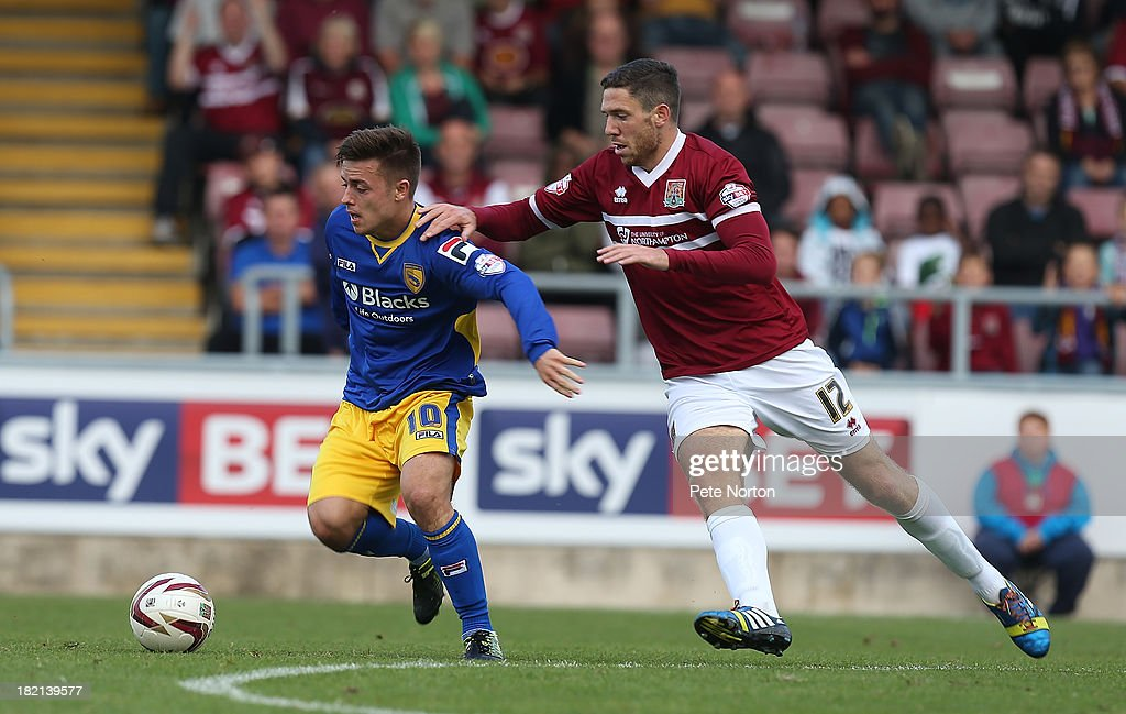 Ryan Williams of Morecambe moves away with the ball from Ben Tozer of Northampton Town during the Sky Bet League Two match between Northampton Town and Morecambe at Sixfields Stadium on September 28, 2013 in Northampton, England.