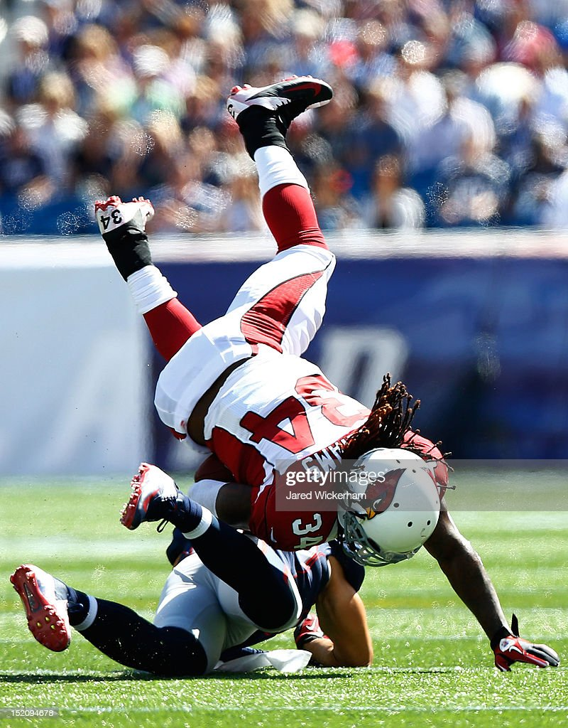 Ryan Williams #34 of the Arizona Cardinals is upended by a New England Patriots defender during the game on September 16, 2012 at Gillette Stadium in Foxboro, Massachusetts.