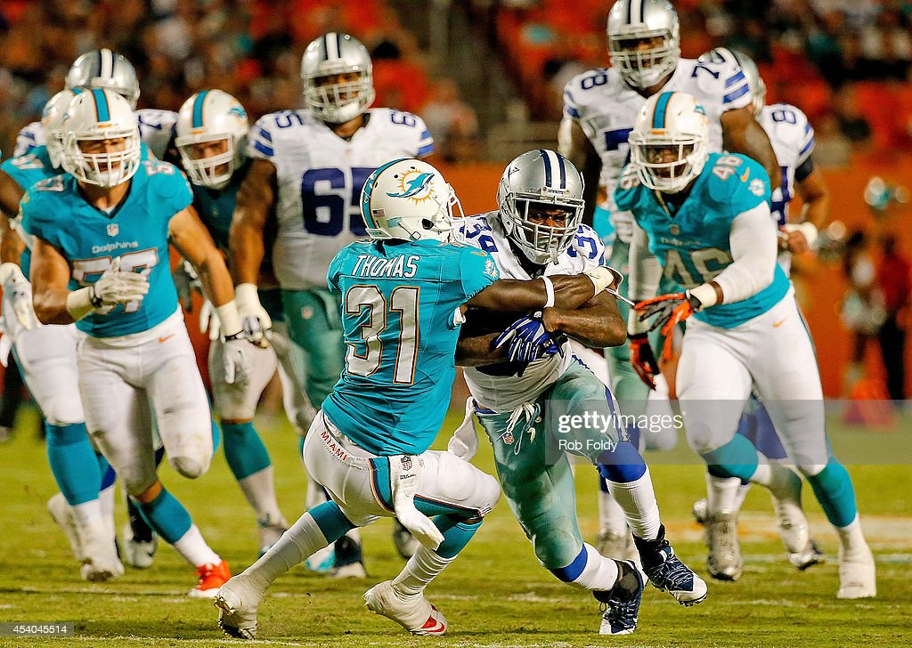 Ryan Williams #34 of the Dallas Cowboys is tackled by Michael Thomas #31 of the Miami Dolphinsduring the game at Sun Life Stadium on August 23, 2014 in Miami Gardens, Florida.