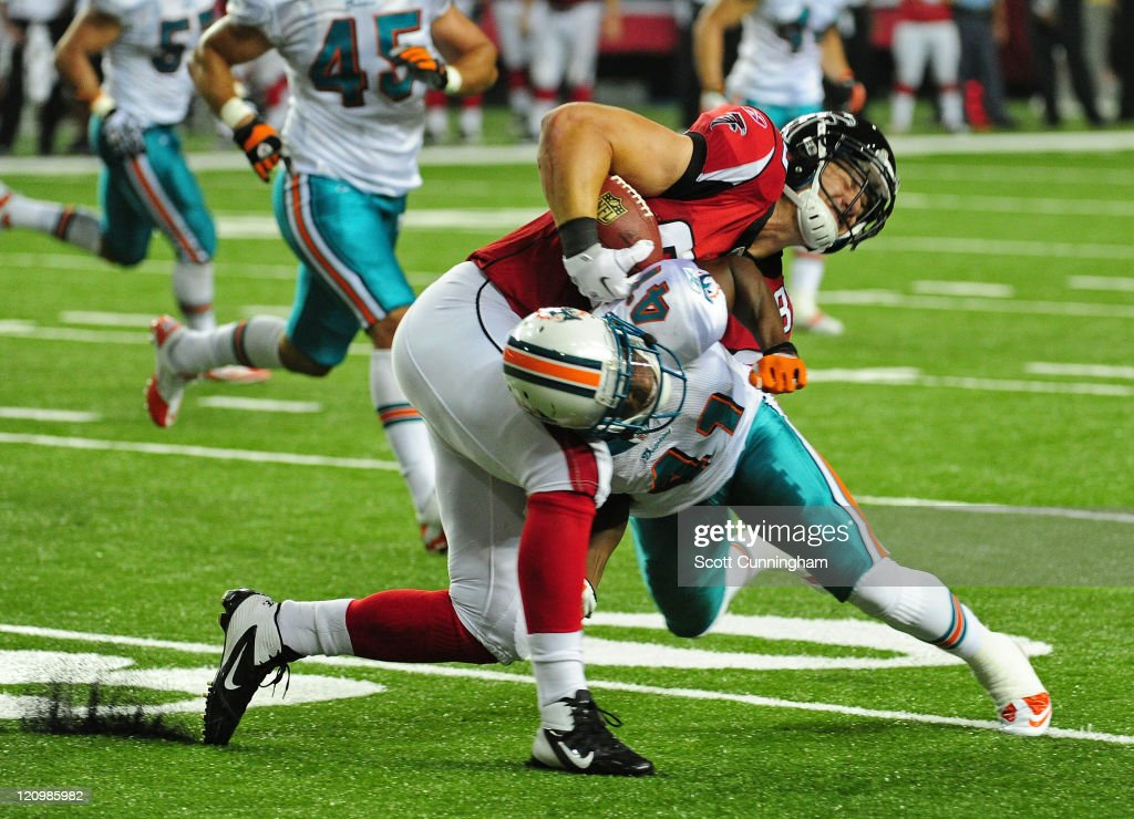 Ryan Winterswyk #86 of the Atlanta Falcons is tackle by Vincent Agnew #41 of the Miami Dolphins during a preseason game at the Georgia Dome on August 12, 2011 in Atlanta, Georgia.