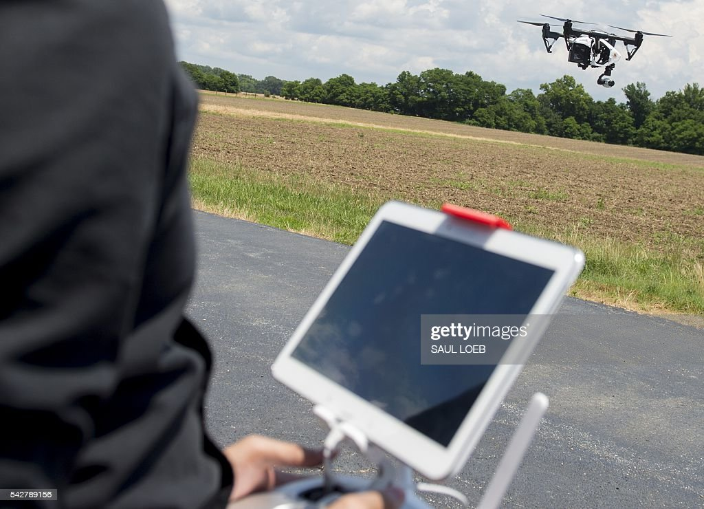 Ryan Wong, an electrical engineering student at the University of Maryland, controls a DJI Inspire drone at a testing site for the University of Maryland's Unmanned Aircraft Systems (UAS) programs in Bushwood, Maryland, June 24, 2016. The Federal Aviation Administration has unveiled new rules that clear the way for small, commercial drones to operate across US airspace. Drone operators will be allowed to fly commercial craft weighing less than 55 pounds (25 kilograms) during daylight hours, provided they can maintain a clear view of the drone at all times. / AFP / SAUL