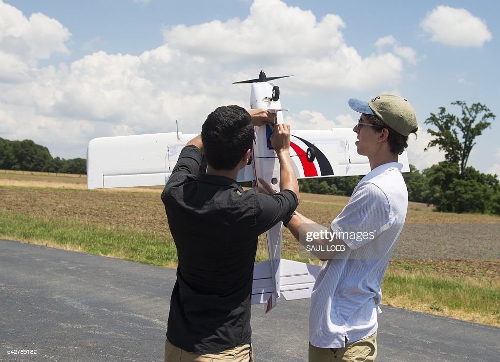 Ryan Wong (L), an electrical engineering student at the University of Maryland, and Joshua Gaus, a mechanical engineering student at UMD, prepare a remote-controlled airplane that has outfitted with autonomous flying controls so that it can fly itself prior to a flight at a testing site for the University of Maryland's Unmanned Aircraft Systems (UAS) programs in Bushwood, Maryland, June 24, 2016. The Federal Aviation Administration has unveiled new rules that clear the way for small, commercial drones to operate across US airspace. Drone operators will be allowed to fly commercial craft weighing less than 55 pounds (25 kilograms) during daylight hours, provided they can maintain a clear view of the drone at all times. / AFP / SAUL