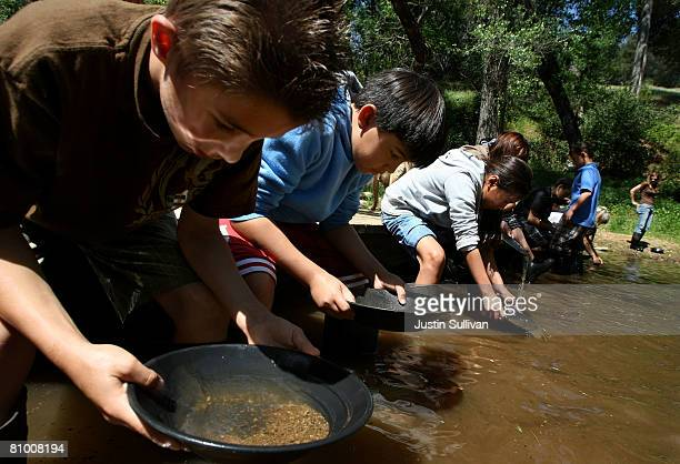 Ryan Yarborough and Jackson DeAndries pan for gold at Gold Prospecting Adventures May 6 2008 on Woods Creek in Jamestown California With gold trading...