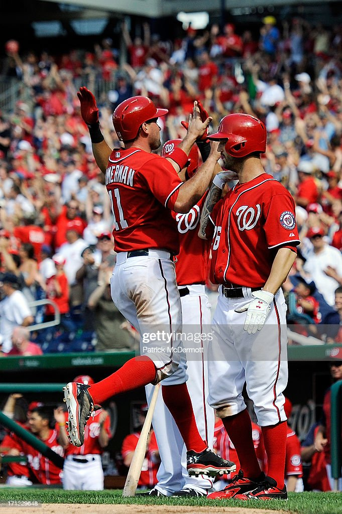 <a gi-track='captionPersonalityLinkClicked' href=/galleries/search?phrase=Ryan+Zimmerman+-+Baseball+Player&family=editorial&specificpeople=534809 ng-click='$event.stopPropagation()'>Ryan Zimmerman</a> #11 celebrates with Jeff Kobernus #26 and <a gi-track='captionPersonalityLinkClicked' href=/galleries/search?phrase=Ian+Desmond&family=editorial&specificpeople=835572 ng-click='$event.stopPropagation()'>Ian Desmond</a> #20 of the Washington Nationals after scoring on a two run RBI double by Jhonatan Solano #23 in the eighth inning during a game against the Colorado Rockies at Nationals Park on June 23, 2013 in Washington, DC.