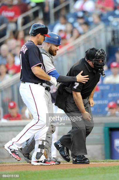 Ryan Zimmerman of the Washington Nationals and Jonathan Lucroy of the Texas Rangers check on home plate umpire Brian O'Nora after he was hit with a...