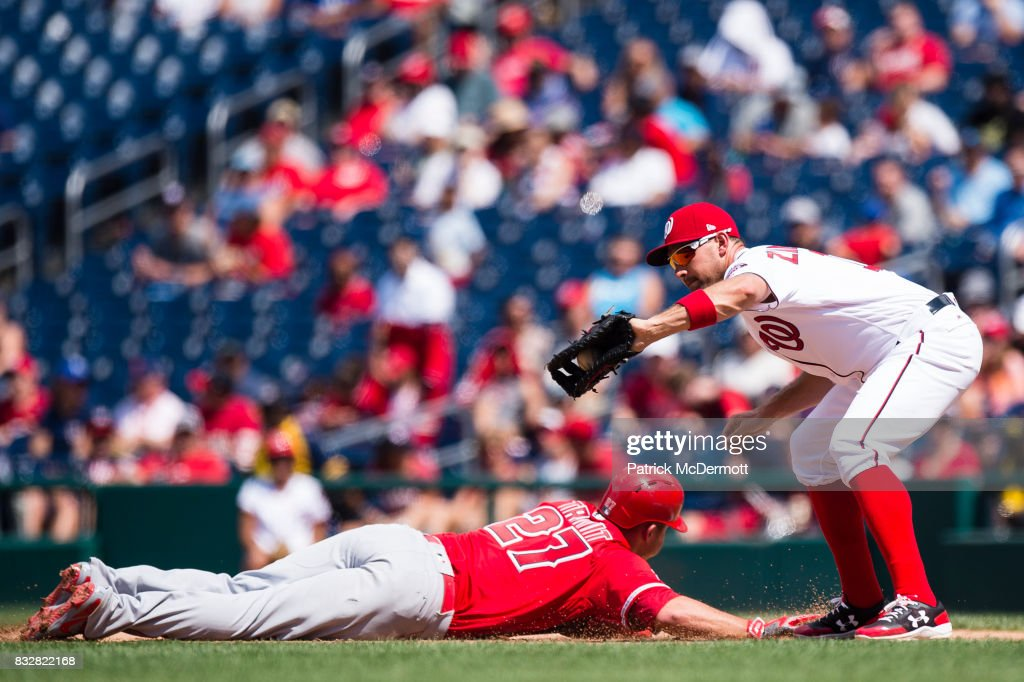 Ryan Zimmerman #11 of the Washington Nationals catches a pickoff attempt as Mike Trout #27 of the Los Angeles Angels of Anaheim dives back to first base in the sixth inning during a game at Nationals Park on August 16, 2017 in Washington, DC.