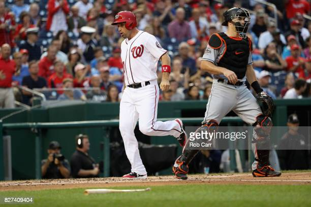 Ryan Zimmerman of the Washington Nationals celebrates after crossing the plate to score a run in front of catcher JT Realmuto of the Miami Marlins in...