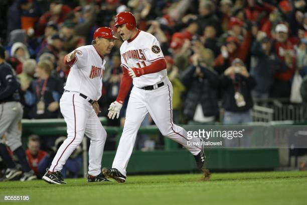 Ryan Zimmerman of the Washington Nationals gets congratulated third base coach Tim Tolman#18 after hitting the game winning homerun in the bottom of...