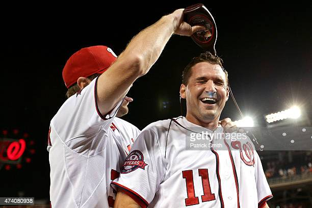 Ryan Zimmerman of the Washington Nationals has chocolate sauce dumped on him by teammate Max Scherzer after hitting a two run walkoff home run in the...