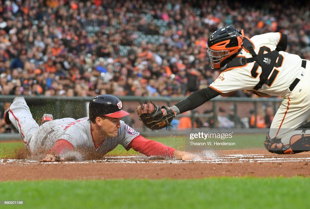 Ryan Zimmerman #11 of the Washington Nationals scores sliding past the tag of Buster Posey #28 of the San Francisco Giants in the top of the first inning at AT&T Park on May 30, 2017 in San Francisco, California.