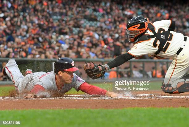 Ryan Zimmerman of the Washington Nationals scores sliding past the tag of Buster Posey of the San Francisco Giants in the top of the first inning at...