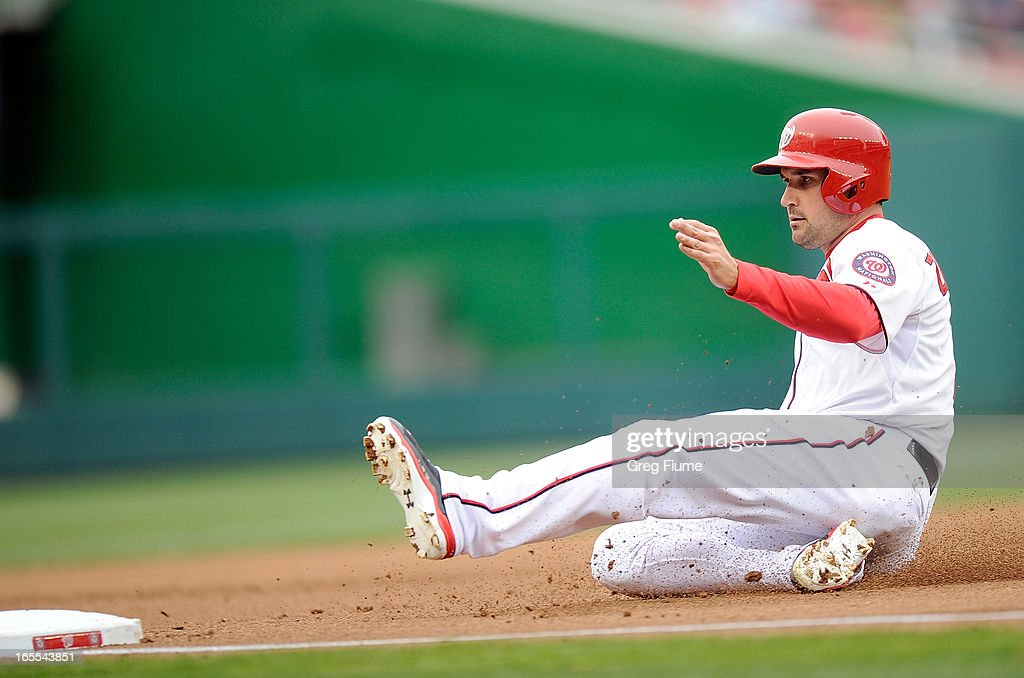 Ryan Zimmerman #11 of the Washington Nationals slides into third base in the first inning against the Miami Marlins at Nationals Park on April 4, 2013 in Washington, DC.