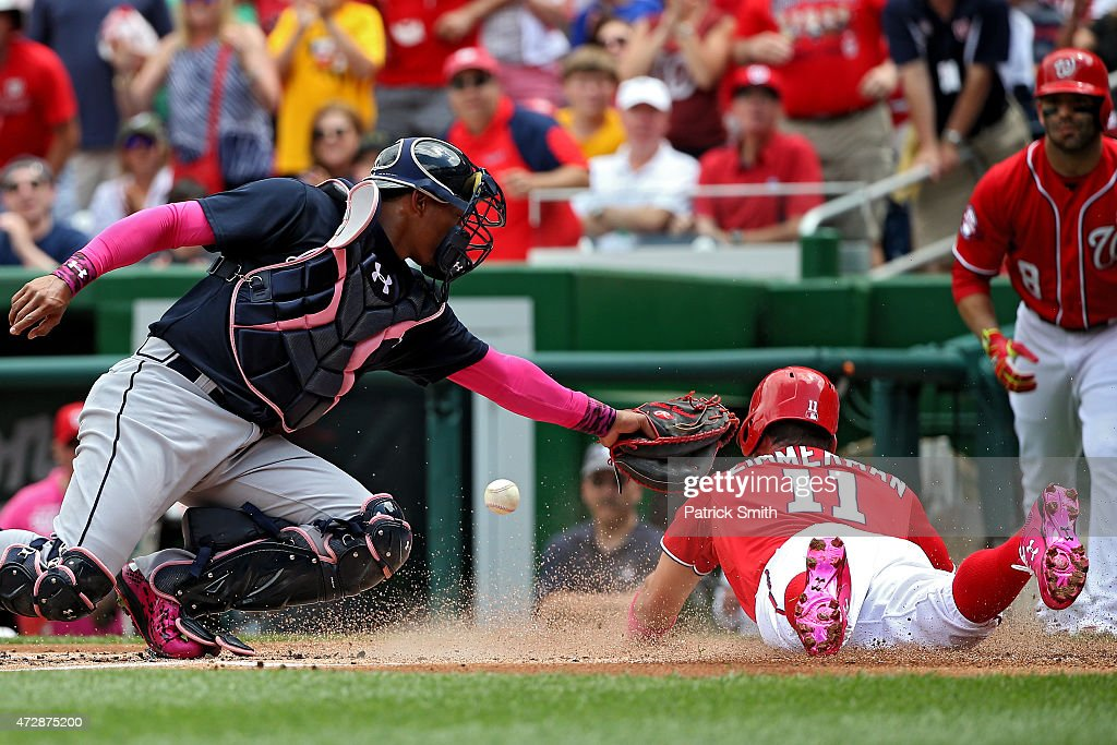 Ryan Zimmerman of the Washington Nationals slides safe at home plate as he beats the tag by catcher Christian Bethancourt of the Atlanta Braves in...