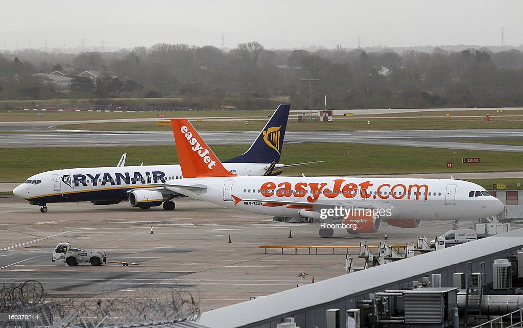 A RyanAir Holdings Plc aircraft taxis past an Airbus A320-214 aircraft, operated by EasyJet Plc, at Manchester airport in Manchester, U.K., on Tuesday, Jan. 29, 2013. Manchester Airports Group, owner of Britain's busiest airport outside London, is buying Stansted from Heathrow Airport Ltd., which is ceding 100 percent of Stansted to comply with regulatory requirements. Photographer: Paul Thomas/Bloomberg via Getty Images