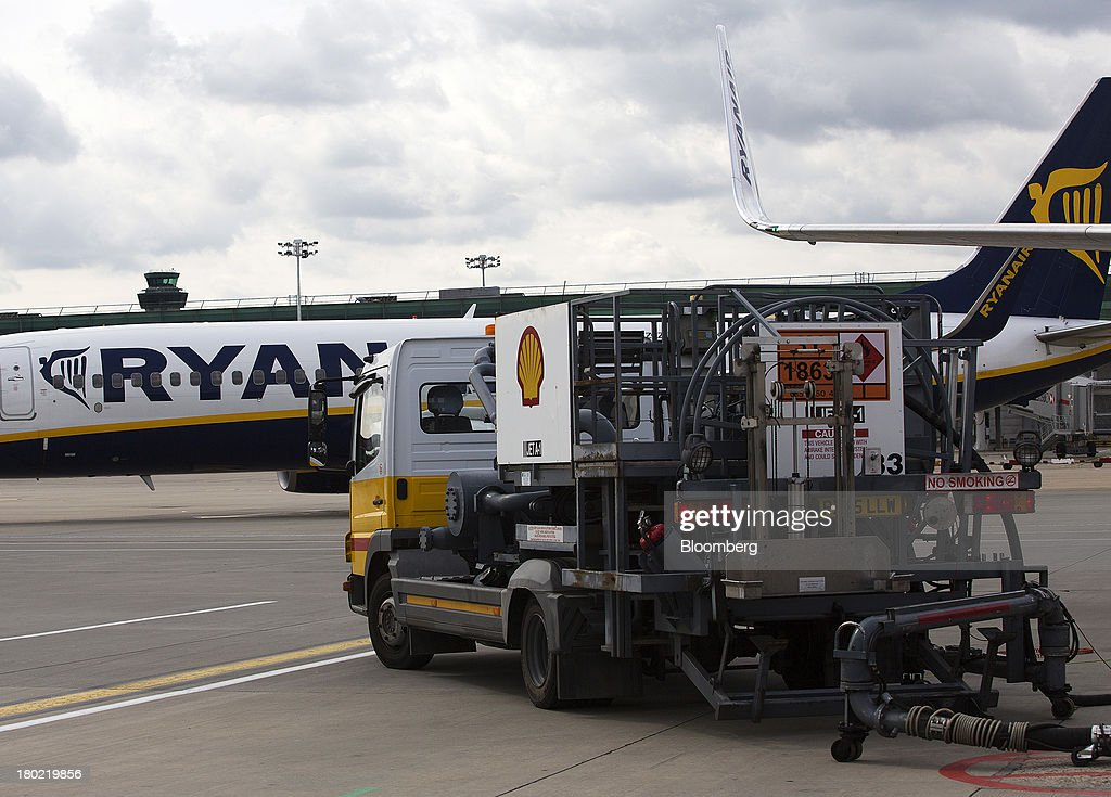 A Ryanair Holdings Plc passenger aircraft passes a Royal Dutch Shell Plc fuel truck at Stansted Airport, operated by Manchester Airports Group (MAG) in Stansted, U.K., on Tuesday, Sept. 10, 2013. From two planes in 1995, EasyJet has grown to more than 200 Airbus SAS aircraft carrying more than 59 million people annually, 20 million fewer than Ryanair. Photographer: Simon Dawson/Bloomberg via Getty Images