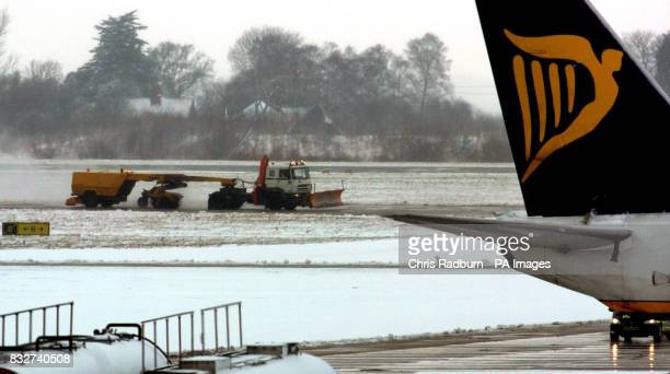 A Ryanair plane wait on the snowcovered tarmac while a snow plough clears snow at Stansted Airport in Essex