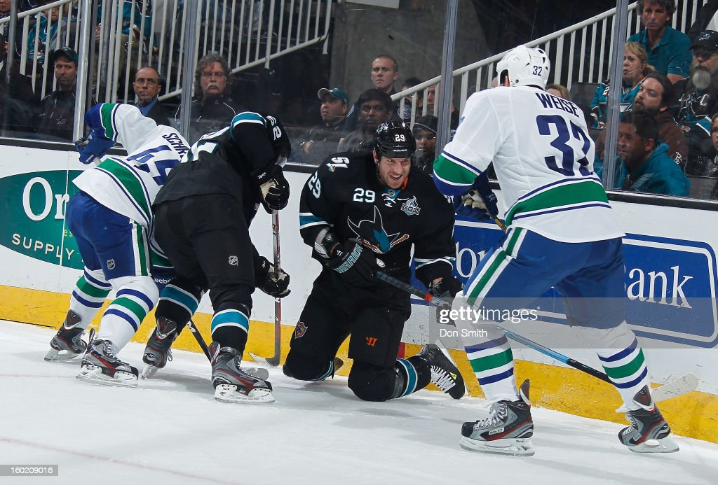 Ryane Clowe #29 and Matthew Irwin #52 of the San Jose Sharks fight for the puck against Dale Weise #32 and Jordan Schroeder #45 of the Vancouver Canucks during an NHL game on January 27, 2013 at HP Pavilion in San Jose, California.
