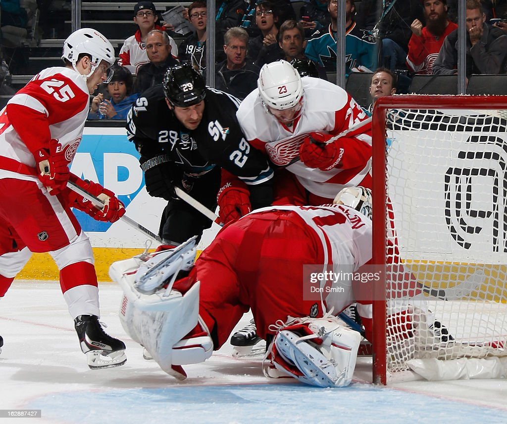 Ryane Clowe #29 of the San Jose Sharks looks for a rebound against Brian Lashoff #23, Cory Emmerton #25 and Jonas Gustavsson #50 of the Detroit Red Wings during an NHL game on February 28, 2013 at HP Pavilion in San Jose, California.