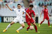 Ryang Yong Gi of DPR Korea challenges Sanjar Tursunov of Uzbekistan during the 2015 Asian Cup match between Uzbekistan and DPR Korea at ANZ Stadium...