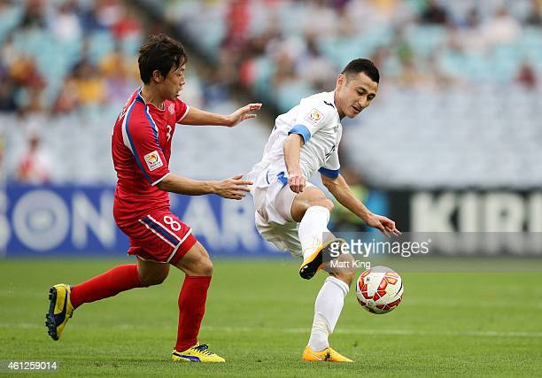 Ryang Yong Gi of DPR Korea challenges Sanjar Tursunov of Uzbekistan during the 2015 Asian Cup match between Uzbekistan and DPR Korea at ANZ Stadium...