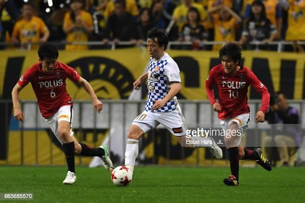 Ryang Yong Gi of Vegalta Sendai controls the ball under pressure of Wataru Endo and Yosuke Kashiwagi of Urawa Red Diamonds during the JLeague J1...