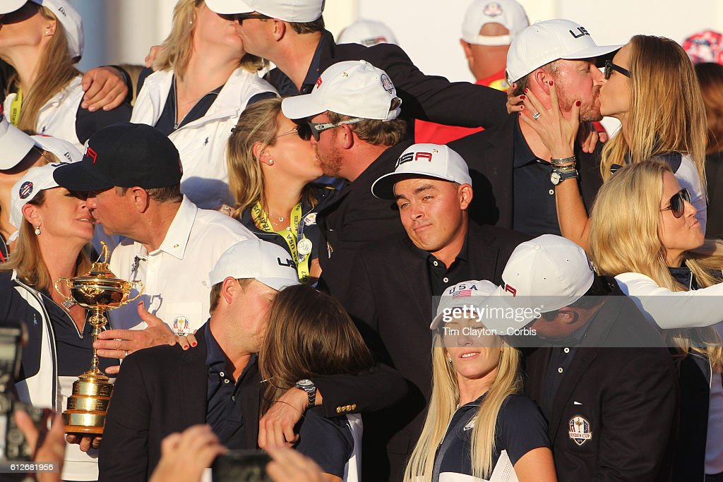 Ryder Cup 2016. Day Three. The United States team players and their spouses and partners kiss as partnerless Rickie Fowler stands alone during Ryder Cup celebrateions after the United States victory in the Ryder Cup tournament at Hazeltine National Golf Club on October 02, 2016 in Chaska, Minnesota.
