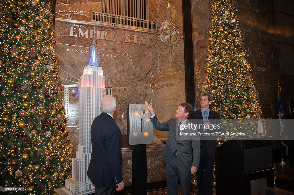 Ryder Cup Captain Tom Watson (C) pulls the lever to light the Empire State Building red, white and blue in the lobby of the Empire State Building on December 13, 2012 in New York City.