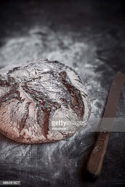 Rye-Spelt-Malt loaf, flour and bread knife on wooden table