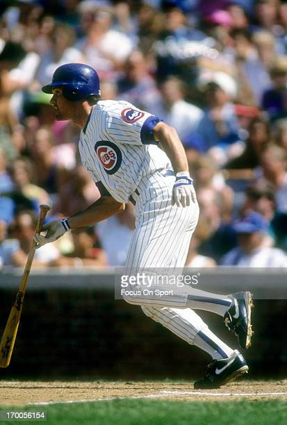 Ryne Sandberg of the Chicago Cubs puts the ball in play and runs towards first base during a MLB baseball game circa 1992 at Wrigley Field in Chicago...