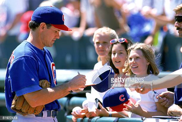 Ryne Sandberg of the Chicago Cubs signs autographs for a group of fans during a game against San Francisco Giants at 3 Comm Park on August 13 1997 in...