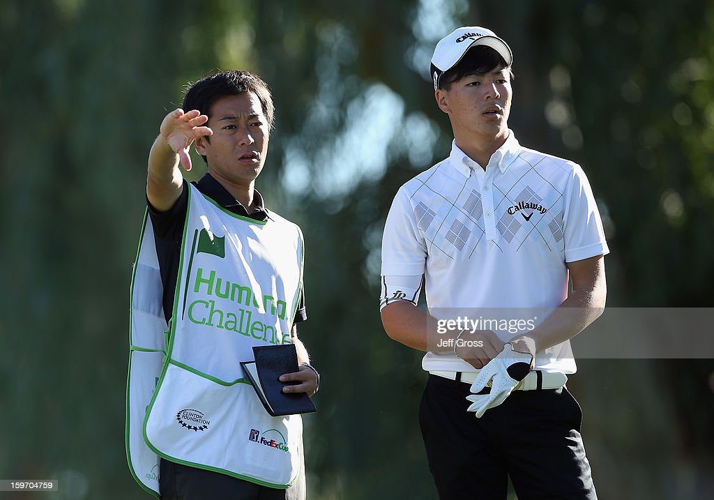 Ryo Ishikawa of Japan and his caddie discuss a tee shot on the 13th hole during the second round of the Humana Challenge In Partnership With The Clinton Foundation at La Quinta Country Club on January 18, 2013 in La Quinta, California.